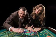 Mężczyzna z kobietą bawić się ruletę przy kasynem Nałóg zdjęcia royalty free