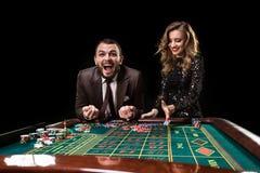 Mężczyzna z kobietą bawić się ruletę przy kasynem Nałóg obrazy stock