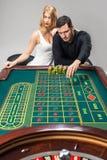 Mężczyzna z kobietami bawić się ruletę przy kasynem fotografia royalty free