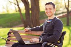 Mężczyzna z komputerową obsiadanie ławką w parku Fotografia Royalty Free