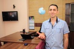 Mężczyzna z kulą ziemską w biurze Zdjęcie Stock