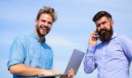 Mężczyzna z laptopem i smartphone rozwiązuje problemy używać mobilnego internet Pracownicy z gadżetami zawsze ma dostęp fotografia stock