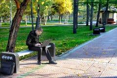Mężczyzna z laptopem przy parkiem Zdjęcia Royalty Free