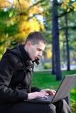 Mężczyzna z laptopem przy parkiem Zdjęcie Stock