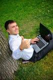 Mężczyzna z laptopem target961_1_ blisko drzewa Obraz Royalty Free