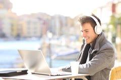 Mężczyzna z laptopu i hełmofonów pracować fotografia royalty free