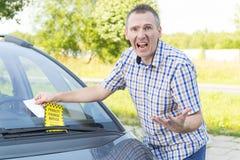 Mężczyzna z mandat za złe parkowanie Obrazy Royalty Free