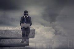 Mężczyzna z maską gazową używa laptop na dachu Fotografia Stock