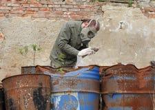 Mężczyzna z maski gazowej i wojskowego ubraniami bada nieżywego ptaka Obraz Stock