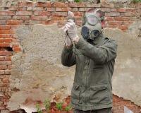Mężczyzna z maski gazowej i wojskowego ubraniami bada nieżywego ptaka Obrazy Royalty Free