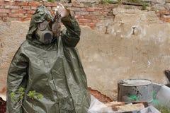 Mężczyzna z maski gazowej i wojskowego ubraniami bada nieżywego ptaka Zdjęcia Stock