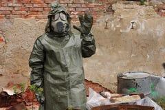 Mężczyzna z maski gazowej i wojskowego ubraniami bada nieżywego ptaka Obrazy Stock