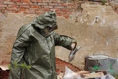 Mężczyzna z maski gazowej i zieleni wojskowego ubraniami bada nieżywego bi Obrazy Stock