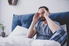 Mężczyzna z migreny obsiadaniem na łóżku obraz stock