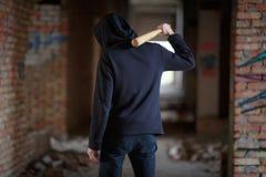 Mężczyzna z nietoperzem na jego ramieniu stoi na zaniechanym budynku Zdjęcia Royalty Free