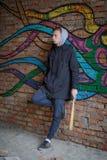 Mężczyzna z nietoperzem w jego rękach stoi na tle graffiti Zdjęcie Royalty Free
