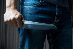 Mężczyzna z nożem w ręce w ciemnym brzmieniu, Obrazy Stock