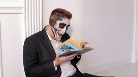 Mężczyzna z okropnym makijażem w formie czaszka trzyma książkę w jego rękach zbiory