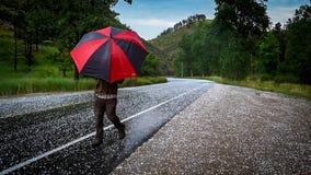 Mężczyzna z parasolem na drodze z gradem zdjęcia stock