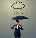 Mężczyzna z parasolowym patrzeje zegarkiem Fotografia Stock