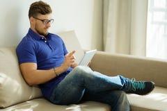 Mężczyzna z pastylka komputerem osobistym w domu Fotografia Stock