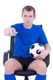 Mężczyzna z pilot do tv dopatrywania meczem futbolowym odizolowywającym na bielu Obrazy Royalty Free