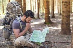 Mężczyzna z plecaka i mapy gmerania kierunkami Fotografia Stock
