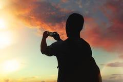 Mężczyzna z plecakiem bierze fotografię piękny zmierzch na smartphone Zdjęcia Stock