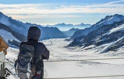Mężczyzna z plecakiem cieszy się na śniegu szczycie zdjęcie stock