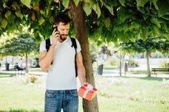 Mężczyzna z plecakiem i prezentem obok drzewa fotografia royalty free