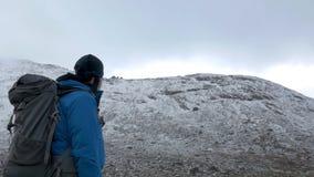 Mężczyzna z plecakiem podróżuje w górach Patrzeje wysokich szczyty i iść dalej zbiory
