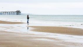 Mężczyzna z połowu słupa połowem na plaży z odbiciem w wodzie zdjęcia royalty free
