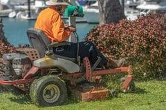 Mężczyzna z pomarańcze odgórną i beżową kapeluszową tnącą trawą zdjęcie royalty free
