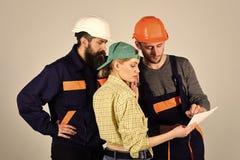 Mężczyzna z poważną emocją Rekrutacyjny pojęcie Brygada pracownicy, budowniczowie w hełmach, naprawiacze i damy dyskutować, fotografia stock