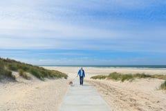 Mężczyzna z psem w krajobraz plaży fotografia royalty free