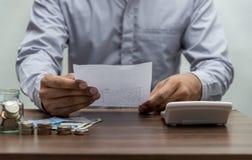 Mężczyzna z rachunkiem i stertą moneta na biznesowego biura stołu roczniku obraz royalty free