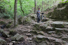 Mężczyzna z rowerem górskim na kamiennej ścieżce w drewnach Obraz Royalty Free