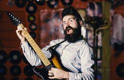 Mężczyzna z rozkrzyczaną twarzą trzyma gitarę, komponuje piosenkę, sztuki muzyka, muzyki świetlicowy tło Rockowego piosenkarza po fotografia stock