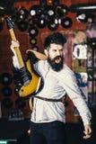 Mężczyzna z rozkrzyczaną twarzy sztuki gitarą, śpiewacka piosenka, sztuki muzyka Muzyk z brody sztuki gitarą elektryczną przeciw  Zdjęcie Stock