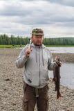 Mężczyzna z rybą na otoczak plaży Syberia, Rosja (Rev 2) obrazy stock