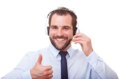 Mężczyzna z słuchawki robi gestowi z jego kciukiem up Obraz Royalty Free