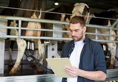 Mężczyzna z schowka i doju krowami na nabiału gospodarstwie rolnym Obraz Royalty Free