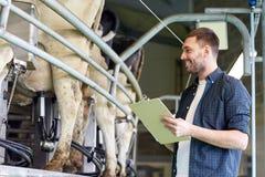 Mężczyzna z schowka i doju krowami na nabiału gospodarstwie rolnym Zdjęcie Stock