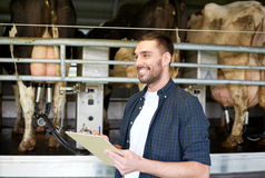 Mężczyzna z schowka i doju krowami na nabiału gospodarstwie rolnym Obrazy Royalty Free