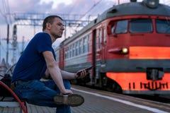 Mężczyzna z smartphone czekaniem dla jego pociągu zatrzymywać pociągi fotografia stock