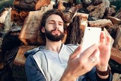 Mężczyzna z smartphone na stosie drewno Obrazy Royalty Free