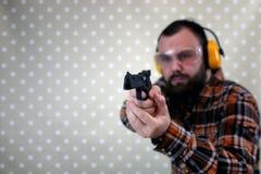 Mężczyzna z stawiającymi dalej ochronnymi gogle i uszaty szkolenie w pistoletowy sh Zdjęcie Royalty Free