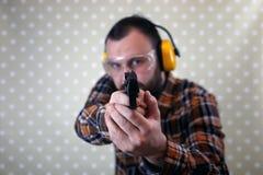 Mężczyzna z stawiającymi dalej ochronnymi gogle i uszaty szkolenie w pistoletowy sh Zdjęcia Royalty Free