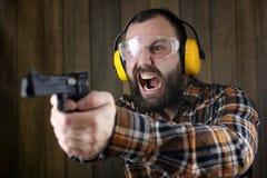 Mężczyzna z stawiającymi dalej ochronnymi gogle i uszaty szkolenie w pistoletowy sh Obraz Royalty Free