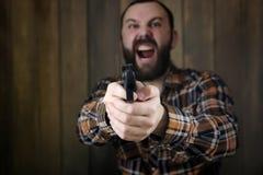 Mężczyzna z stawiającymi dalej ochronnymi gogle i uszaty szkolenie w pistoletowy sh Obraz Stock